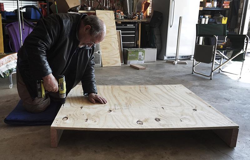 John drives screws as he builds platform. ©2016 Eileen Blass